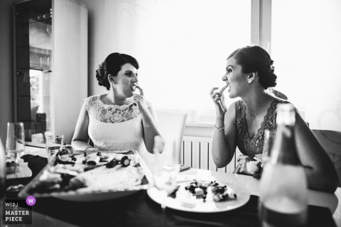 Bride and maid of honor checking each others teeth at the wedding reception in Ruse, Slovenia