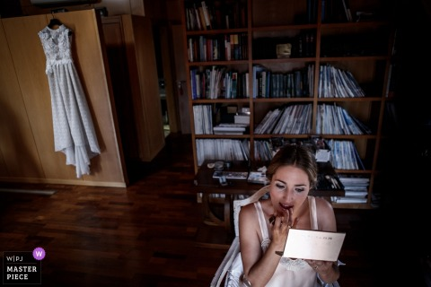 Bride doing her makeup before the wedding ceremony with her dress hanging behind her in Ubeda