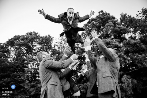 Groomsmen throw the groom into the air outside at the wedding reception in Vermont