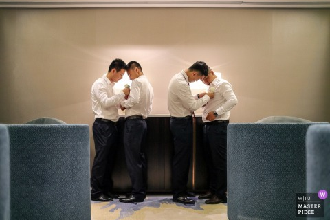 China groom and groomsmen helping each other get ready before the wedding ceremony