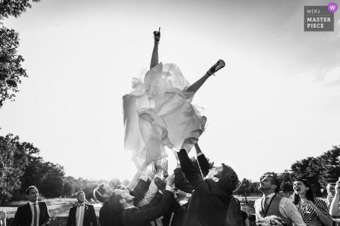Gasten gooien de bruid buiten op de bruiloftsreceptie in Parijs - Frankrijk