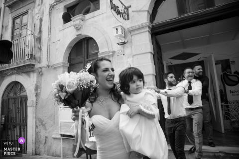 Bride holds the flower girl outside after the wedding ceremony in Siracusa