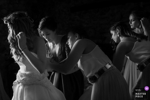 Bridesmaids helping the bride with her wedding dress before the ceremony in Alcoy