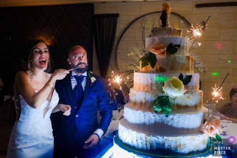 Alcoy bride and groom smile next to the wedding cake at the reception