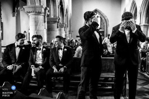 Groom and best man wiping off sweat at the wedding ceremony in Waddesdon, UK