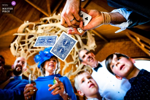 Groom shows guests a magic trick with a deck of cards at the wedding in Waddesdon Dairy, UK