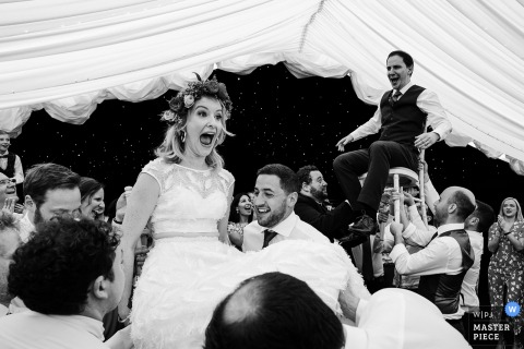 Guests lift up the bride and groom in their chairs at the wedding reception in Cheshire, England