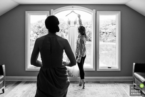 New Jersey bride hanging her dress in front of the window