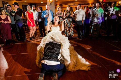 Bride laughs as the groom gets the garter at the wedding reception at Lake Tahoe, Ca