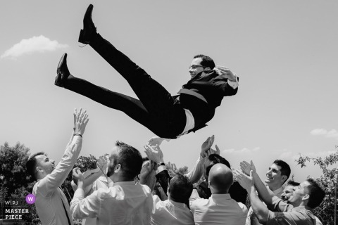Guests lift the groom into the air outside at the wedding reception in Segovia