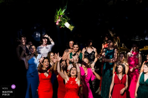 Guests reach for the bouquet at the wedding reception in Braga, Portugal