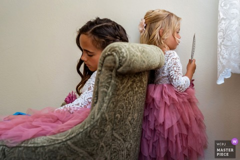 Flower girls sit and wait before the wedding ceremony in San Diego, California