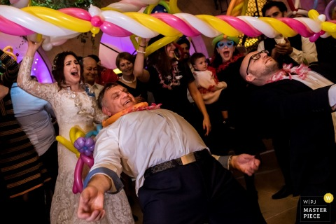Bride and groom play limbo at the wedding reception in Israel- Jerusalem