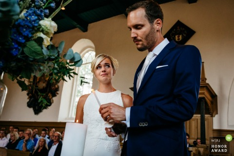 Oenkerk bride and groom lighting a candle during their church wedding ceremony