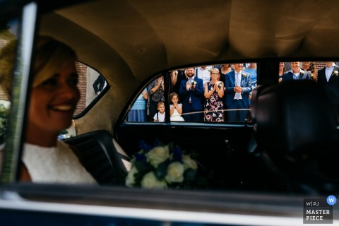 Oenkerk bride smiles in the car on her way to the wedding ceremony