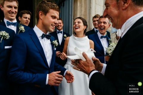 Bride and groom laugh before releasing the pigeon in lede - Netherlands wedding photographer