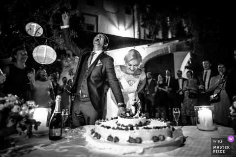 Bride and groom smile as they cut the wedding cake in Castello Di Montegufoni, Italy