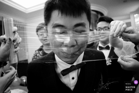 Bridal party putting wrap on the grooms face at the wedding in China