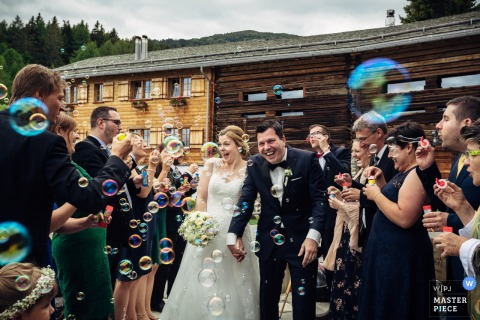 Guests blow bubbles outside  at the bride and groom after the wedding in Guarda Val, Switzerland