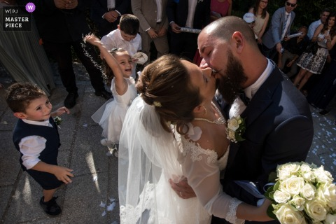 Mantova bride and groom kiss in front of some kids at the wedding reception