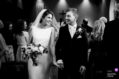Bride and groom smile at each other as they walk down the aisle after the wedding ceremony in Kildare, Ireland