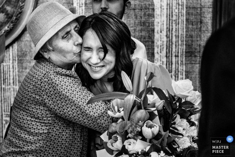 Romania bride gets a hug and a kiss from her mother after the wedding ceremony