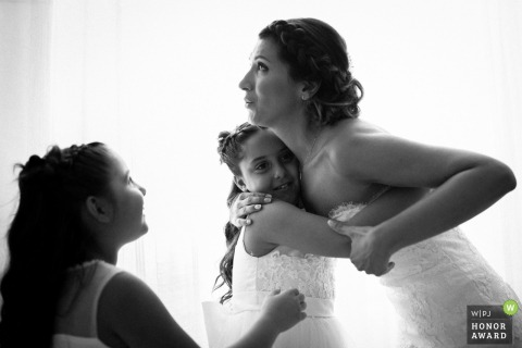 Une mariée romaine embrassant des demoiselles d'honneur junior avant la cérémonie de son mariage