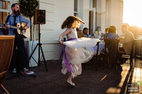 Little girl dances in the sunlight at the outdoor wedding reception in Dublin