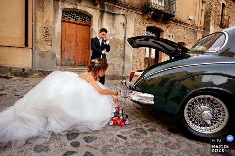 Calabria bride outside hooking cans with the groom on the back of the car after the wedding