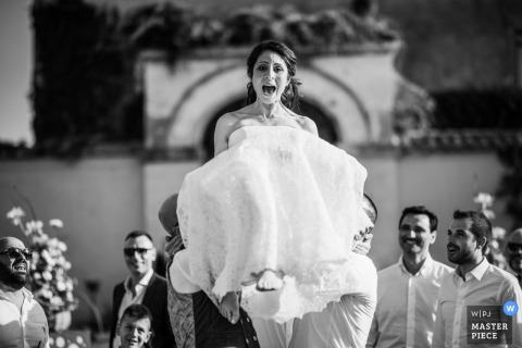 Guests lift the bride into the air outside at the wedding reception in Roma, Italy