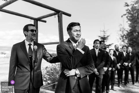Outdoor photo of the groom getting emotional as he sees the bride during the wedding ceremony in Tahoma, CA