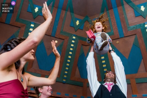 Groom lifts the flower girl in the air at the wedding reception in Graeagle, CA