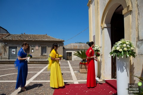 Cosenza bridesmaids in blue yellow and red dresses getting ready to walk into the church a Sunny day