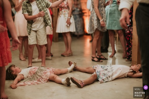 Little kids lay on the floor while surrounded by guests at the wedding reception in Bulverde, Texas