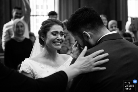 Bride smiles as the groom gets emotional during the wedding ceremony in London, UK