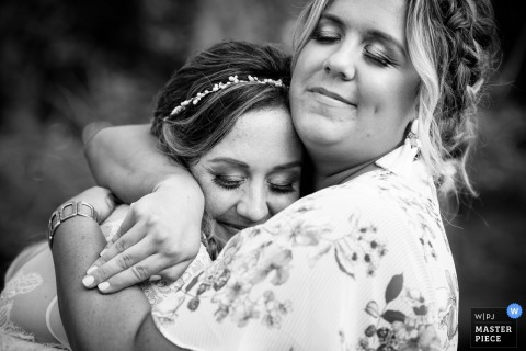 Bride hugs her sister during her wedding at Meyers Castle.