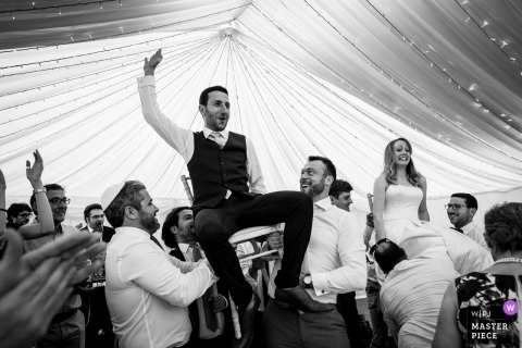 Guests lift up the bride and groom in their chairs at the wedding reception in reading, UK