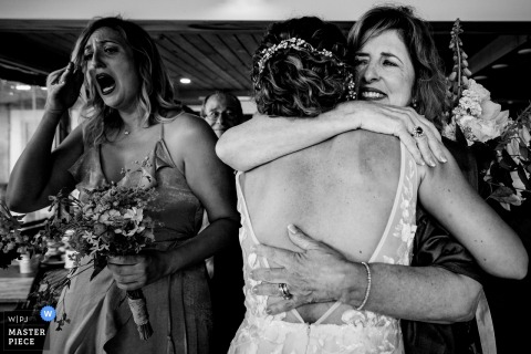 Boothbay Harbor Maine Bride hugs her mother-in-law as her bridesmaid wipes away tears of happiness at the end of the ceremony | Linekin Bay Resort Boothbay Harbor Maine