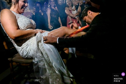 Groom getting the garter from the bride at the wedding reception in Goiânia