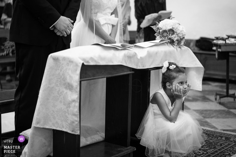 Tuscany flower girl sits in front of the bride and groom during the wedding ceremony