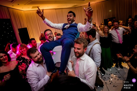 England groomsmen left the groom into the air at the wedding reception