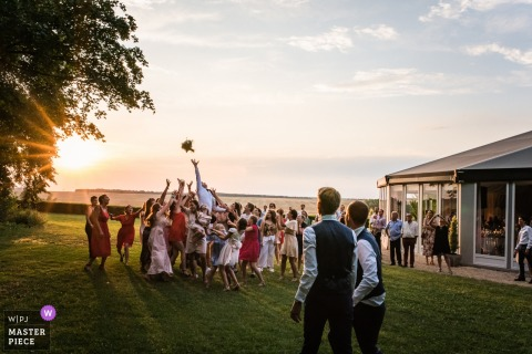 Outdoor photo of guests reaching for the bouquet at the sunset wedding reception in Dangy Centre Val De Loire