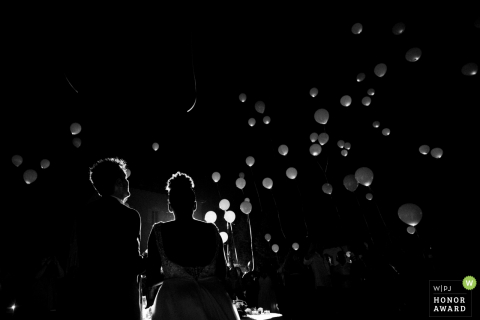 Bride and groom watch the balloons at the nitetime reception - Emilia-Romagna wedding photojournalism