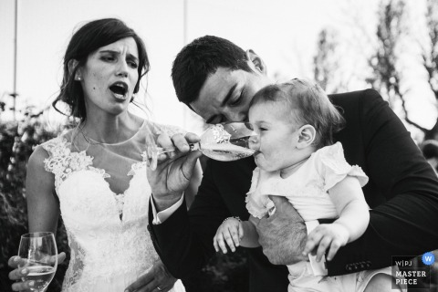 Modena groom gives baby a drink next to the bride at the wedding reception