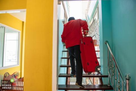 Ayutthaya, Thailand Der Bräutigam trägt einen großen Koffer. Eine Treppe