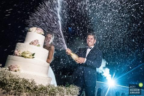 Groom knalt een fles champagne naast de taart - Lecco trouwfotograaf
