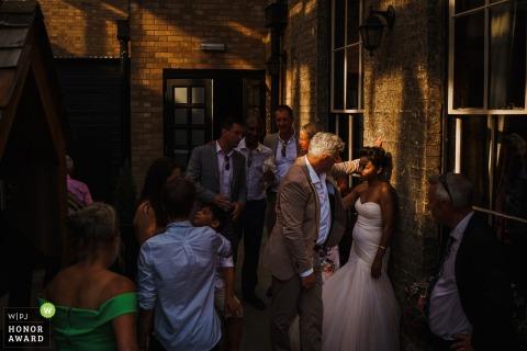 Braut, Bräutigam und Gäste mischen sich im sonnigen Innenhof des Hotel Du Vin in Cambridge, UK, Hochzeitsempfang