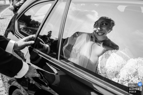 Bride in the car smiles before the wedding in le pinete Viggiù