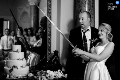 Bride holds a sword to cut the wedding cake at the reception in Carlow, Ireland