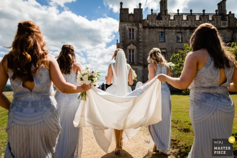 Bridesmaids hold the brides dress outside before the wedding ceremony in Carlow, Ireland